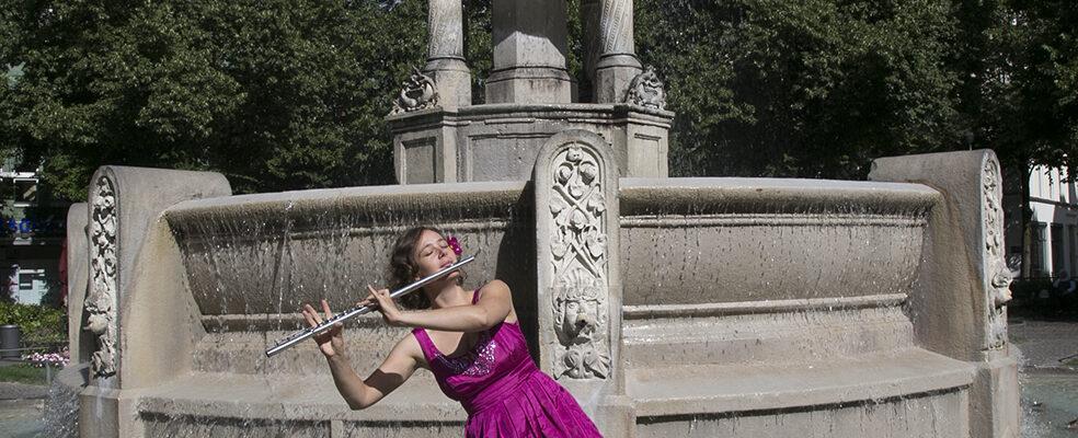 Jasmin Gundermann mit ihrer Querflöte im Brunnen in München
